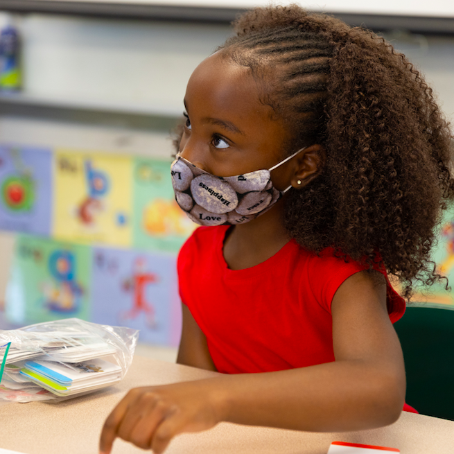 Young girl in mask with school work